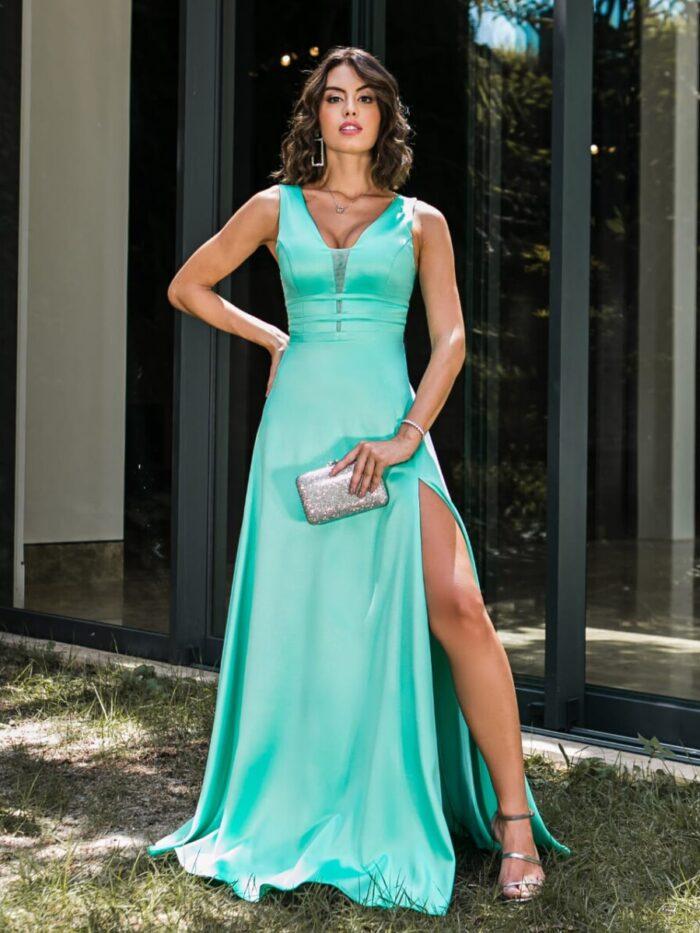 Vestido de verde Tiffany, decote regata e saia com fenda.